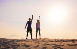 Человек и женщина фитнеса с оружиями вверх по праздновать цели спорта стоковые изображения