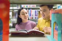 Человек и женщина читают и говорят открытую книгу на книжных полках Стоковые Фотографии RF