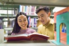 Человек и женщина читают и говорят открытую книгу на книжных полках Стоковые Изображения RF