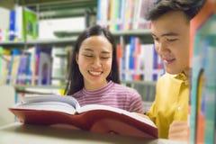 Человек и женщина читают и говорят открытую книгу на книжных полках Стоковое Фото
