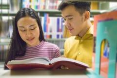 Человек и женщина читают и говорят открытую книгу на книжных полках Стоковое фото RF