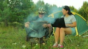 Человек и женщина outdoors и мясо приготовления на гриле на гриле деятельность женщины компьтер-книжки видеоматериал