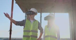 Человек и инженеры женщины на строительной площадке в стеклах VR управлять конструкцией здания обсуждая a видеоматериал