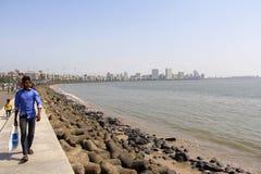 Человек и люди идя вдоль бортового морского привода, рискованного предприятия с морем и зданий стоковое фото