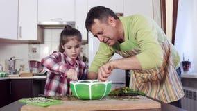 Человек и маленькая дочь с ингредиентами смешивания каштановых волос акции видеоматериалы