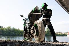 Человек и мотоцикл велосипедиста с предпосылкой реки, отключением moto всадника на улице на береге реки, наслаждаясь свободой и стоковое фото