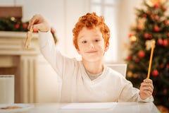Человек и усмехаться пряника очаровательного мальчика redhead поднимаясь Стоковые Фото