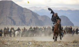 Человек казаха на лошади комплектуя вверх монетки от земли стоковое фото rf