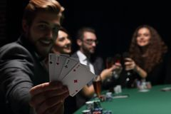 Человек картежника в казино сидя на таблице с карточками и обломоками покера Стоковые Фотографии RF