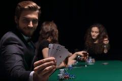 Человек картежника в казино сидя на таблице с карточками и обломоками покера Стоковая Фотография