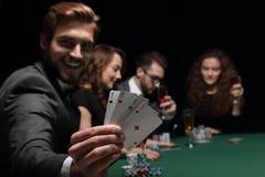 Человек картежника в казино сидя на таблице с карточками и обломоками покера Стоковое Фото