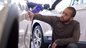 Человек касается крылу автомобиля на дилерских полномочиях стоковое изображение rf
