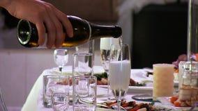 Человек кельнера льет игристое вино шампанского белое в стекло Подъемы пены Ресторан видеоматериал