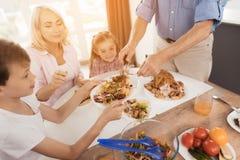Человек кладет вне испеченного индюка к его родственникам, которые сидят на праздничной таблице на благодарение стоковые фото