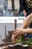 Человек кладет горящие ручки ладана в специальный шар Стоковые Фото