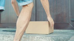 Человек кладет коробку около двери сток-видео