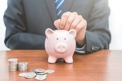 Человек кладет монетки в Piggy концепцию сбережений банка- стоковое фото