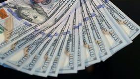 Человек кладет стог 100 долларовых банкнот на таблицу видеоматериал