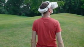Человек кладет шлемофон VR на его голову в парк и смотрит вокруг акции видеоматериалы