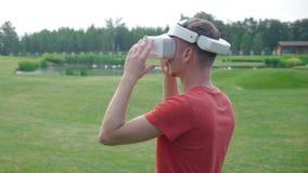 Человек кладет шлемофон VR на его голову в парк и смотрит вокруг видеоматериал