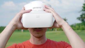 Человек кладет шлемофон VR на его голову в парк видеоматериал