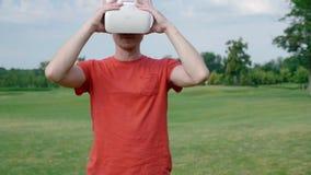 Человек кладет шлемофон VR на его голову в парк сток-видео