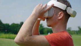 Человек кладет шлемофон VR на его голову в парк акции видеоматериалы