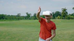 Человек кладет шлемофон VR на его голову и игру виртуальной игры в парк акции видеоматериалы