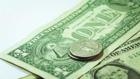 Человек кладя 2 башни монеток на 2 долларовые банкноты