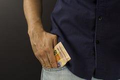 Человек кладя бразильские деньги внутри карманн Стоковое фото RF