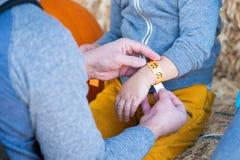 Человек кладя бумажный браслет на руку childs стоковые фото