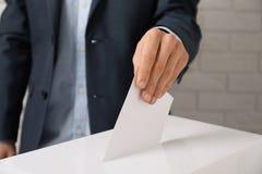 Человек кладя его голосование в урну для избирательных бюллетеней против кирпичной стены стоковая фотография rf