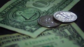 Человек кладя 4 монетки на 2 долларовые банкноты