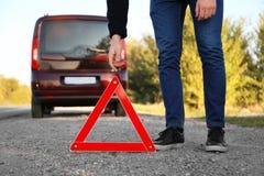 Человек кладя предупреждающий треугольник на дорогу асфальта emergency стоковые изображения rf