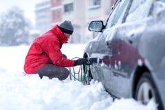 Человек кладя цепи снега на автошину автомобиля стоковая фотография rf
