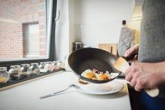 Человек кладя яичницы на плиту стоковое фото rf