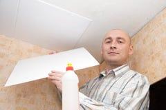 Человек клеит плитку потолка Стоковая Фотография