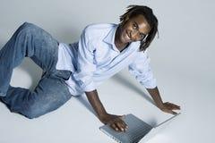 человек компьтер-книжки афроамериканца используя детенышей Стоковые Фото