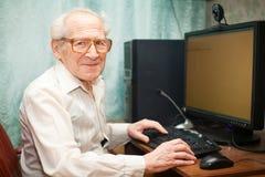 человек компьютера около старший усмехаться Стоковая Фотография