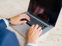 Человек конца-вверх печатая на цифровой компьтер-книжке на светлой предпосылке Полезная концепция электроники Стоковое Изображение RF
