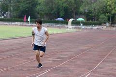 Человек красивого спортсмена азиатский бежать на беговой дорожке в стадионе с предпосылкой космоса экземпляра Здоровая активная к Стоковые Фото