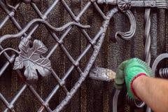 Человек красит строб с выкованными элементами На его руке зеленая перчатка, около локтя пасти стоковые изображения