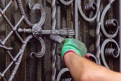 Человек красит строб с выкованными элементами На его руке зеленая перчатка, около локтя пасти стоковая фотография