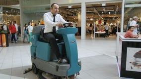 Человек крупного плана управляет машиной чистки вдоль торгового центра сток-видео