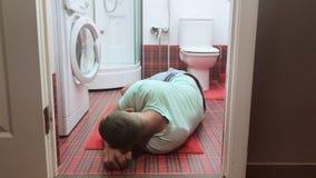 Человек лежал на поле bathroom, рядом с туалетом после передозировки алкоголя или лекарств видеоматериал