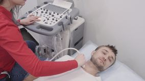 Человек лежа во время проходить диагностику ультразвука для тиреоида сток-видео