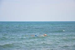 Человек лежит на воде в море Стоковая Фотография