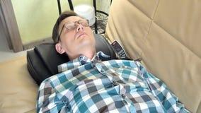 Человек лежит на кресле дома, под головой massager, ослабленное положение видеоматериал