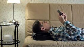 Человек лежит на кресле дома, под головой massager, ослабленное положение акции видеоматериалы