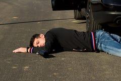 Человек лежит рядом с бутылкой на дороге за черным автомобилем и предупреждающим треугольником стоковое изображение